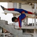 加沙男童在战火废墟上表演高难度体操