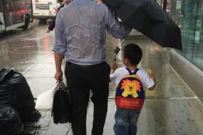 爸爸全身湿透为儿撑伞感动网友
