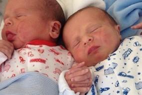 刚出生双胞胎紧握双手似在相互鼓励