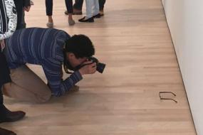 小伙将眼镜放艺术馆墙根 游人纷纷围观拍照