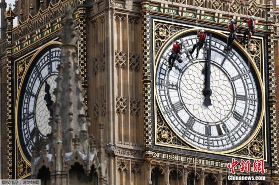 当地时间2014年8月18日,英国伦敦,工作人员吊在大笨钟钟面上进行清洁工作。-趣闻巴士