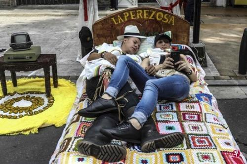世界懒人日当天,伊塔圭一对伴侣将床搬到大街上,准备悠闲地度过这一天。-趣闻巴士