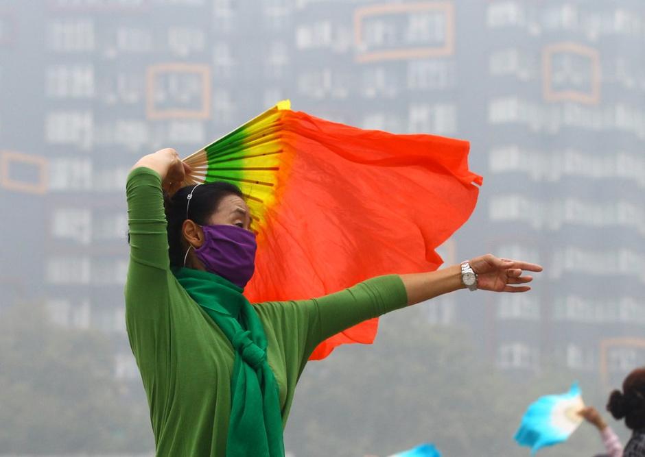 2014年10月9日上午,河南郑州,一名晨练的女士在戴着口罩跳扇子舞。
