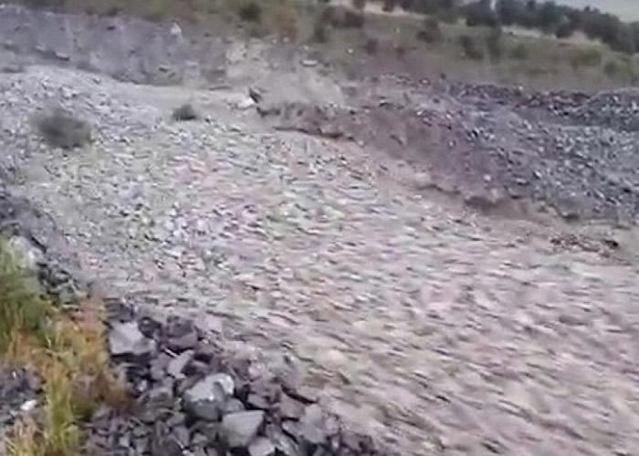 大量灰色的碎石沿着斜坡滚下。